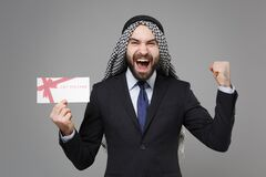 Joyful bearded arabian muslim businessman in keffiyeh kafiya ring igal agal suit isolated on gray background