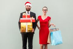 Joyful bearded business man in red hat and business woman in red Stock Images