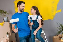 Joyful bearded father and little daughter plan to paint wall with rollers in yellow. stock photography