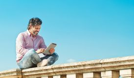 Joyful bearded man with digital tablet outdoors browsing to his wife Stock Images
