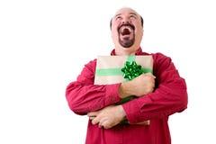 Joyful bearded man holding Christmas gift Royalty Free Stock Images