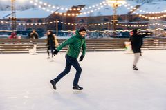 Joyful bearded man practices going skating on ice ring, has cheerful expression, smiles happily, demontrates his professionalism. Active sporty male in green royalty free stock images