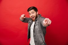 Joyful bearded man 30s in jeans jacket looking on camera with po. Inting index fingers on you  over red background Royalty Free Stock Image