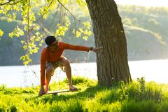 Joyful bearded man is training on the balance board. And having fun on a green meadow next to river on sunny evening. Back light, front view Stock Images