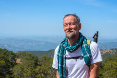Joyful bearded man, traveler stands in the mountains. Admiring the beautiful views. Sunny day on Troodos, Cyprus Stock Photos