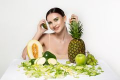 Joyful beautiful girl with bright art makeup holding sliced fresh avocado in hand near face, fruits in front. Healthy stock photos