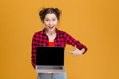 Joyful beautiful woman holding and pointing on blank screen laptop Royalty Free Stock Image