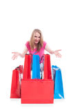 Joyful beautiful woman sitting next to colorful shopping bags Stock Images