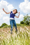 Joyful beautiful young girl jumping, dancing in high dry grass Royalty Free Stock Photo