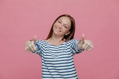 Joyful beautiful young lady raises thumbs at camera, shows that everything is okay, wears striped clothes, tilts head, smiles royalty free stock image