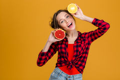 Joyful beautiful young woman holding halves of citrus fruits Royalty Free Stock Photo