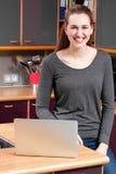 Joyful beautiful young woman with laptop in kitchen for telecommuting. Joyful beautiful young woman with laptop in her kitchen for telecommuting, shopping online stock photo
