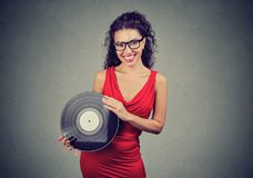 Smiling beautiful young woman showing a vintage vinyl Stock Images