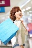 Joyful beauty in shop. Joyful woman standing in a half-turn in shop with bags Stock Image