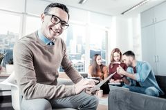 Joyful bespectacled man holding the document and looking straight. Everything is fine. Joyful bespectacled pleasant men sitting in the room on the chair holding Stock Image