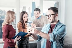 Joyful bespectacled man standing and using the smartphone. New message. Joyful pleasant bespectacled men standing in the room near his colleagues smiling and Stock Images