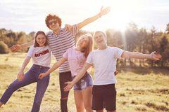 Joyful best fellows celebrate something outdoor, have picnic, stretch hands happily, give hug at camera, foolish on meadow, pose a. Gainst blue sky background Stock Photography