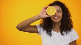 Joyful biracial girl holding orange and smiling healthcare and vitamins skincare. Stock footage stock video
