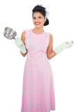 Joyful black hair model holding a pan and wearing rubber gloves Royalty Free Stock Photos