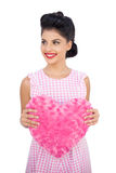 Joyful black hair model holding a pink heart shaped pillow Stock Photos