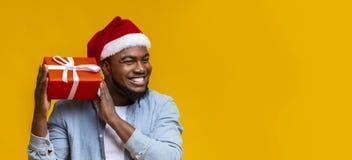 Free Joyful Black Man In Santa Hat Shaking Christmas Gift Box Royalty Free Stock Image - 164359716