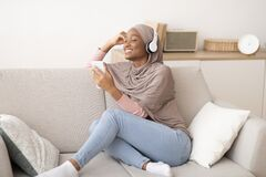 Free Joyful Black Muslim Woman In Hijab And Headphones Listening To Music On Cellphone, Closing Her Eyes In Delight, At Home Stock Photography - 206670682