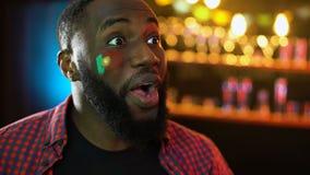 Joyful black soccer fan with portuguese flag on cheek celebrating match victory. Stock footage stock footage