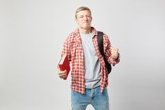 Joyful blond guy with black backpack on his shoulder dressed in a white t-shirt, red checkered shirt and jeans holds royalty free stock photos