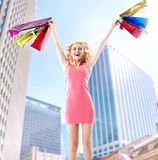 Joyful blond woman jumping with paper bags Stock Photography