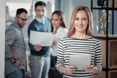 Joyful blond woman standing with her tablet stock images