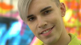 Joyful blond young male with nose and ear rings smiling on camera, subculture stock footage