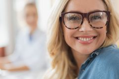 Joyful blonde attractive woman expressing true positivity. Positive beautiful woman smiling while her ophthalmologist sitting in the background stock image