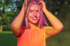 Joyful blonde girl having fun with colorful dry paint at the park. Concept for festival Holi. Joyful blonde woman having fun with colorful dry paint at the park royalty free stock images