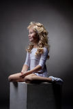 Joyful blonde gymnast posing on cube in studio Royalty Free Stock Photos