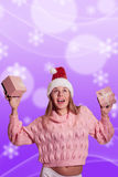 Joyful blonde lady in Santa hat holding two Stock Photography