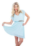Joyful blonde model in blue dress posing holding her dress Royalty Free Stock Images