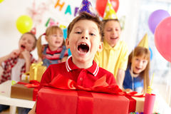 Joyful boy. With big red giftbox looking at camera with his friends on background Royalty Free Stock Photography