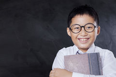 Joyful boy with book and blackboard Stock Photography