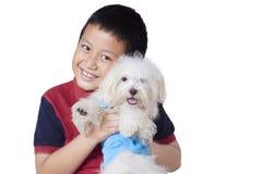 Joyful boy embrace his dog in studio Stock Photo