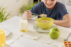 Joyful boy enjoying breakfast in kitchen. I like healthy food. Happy male kid is eating cereals and milk with enjoyment. He is sitting at table and smiling Royalty Free Stock Images