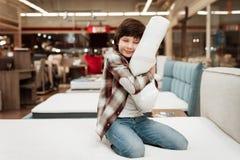 Joyful boy enjoying softness of orthopedic pillow rejoices in furniture store. Joyful little boy hugs orthopedic pillow sitting on mattress Stock Images