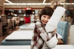 Joyful boy enjoying softness of orthopedic pillow rejoices in furniture store. Joyful little boy hugs orthopedic pillow sitting on mattress Royalty Free Stock Photography