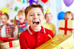 Joyful boy. With giftbox looking at camera with his friends on background Stock Images