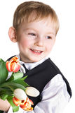 Joyful boy gives beautiful tulips Royalty Free Stock Images