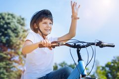 Joyful boy greeting somebody while riding bicycle. Oh hello there. Low angle shot of a charming kid grinning broadly while holding his bicycle and lifting his Royalty Free Stock Images