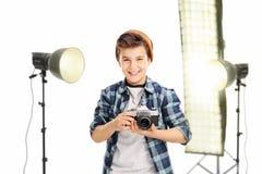 Joyful boy holding a camera in a studio. Joyful little boy holding a camera and standing in a studio with lighting equipment isolated on white background royalty free stock photos