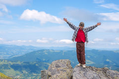 Joyful boy with open arms stands on the cliff in the mountain. Happiness and success in nature Royalty Free Stock Photography