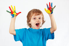 Joyful boy with painted hands on white background stock photo