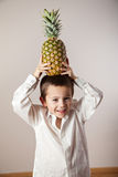 Joyful boy with a pineapple on his head Royalty Free Stock Photography