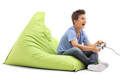 Joyful boy playing video games. And laughing seated on a green beanbag isolated on white background Stock Photos